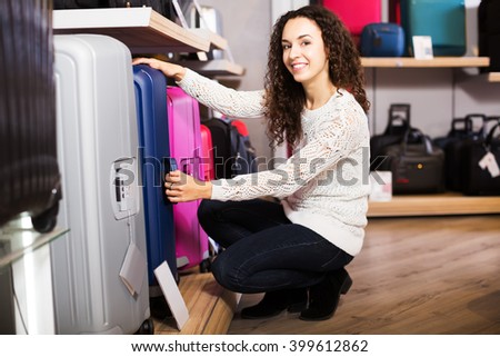 Young happy woman choosing travel suitcase in haberdashery shop