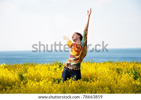 Young happy woman dancing in yellow flowers - stock photo