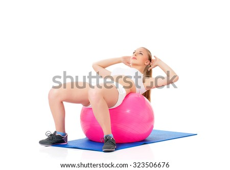 Young happy woman doing fitness exercise with fitness-ball, isolated on white background - stock photo