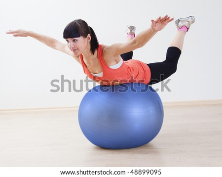 Young happy woman doing fitness exercises with ball - stock photo