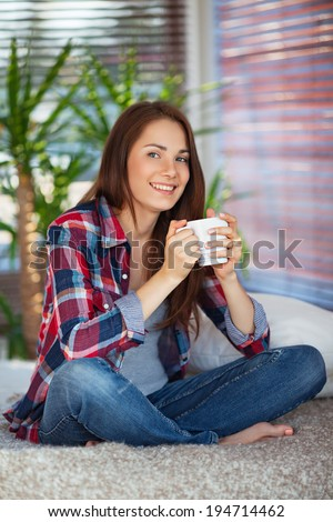Young happy woman drinking coffee / tea on sofa at home - stock photo