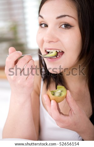 young happy woman eating fruit in bed
