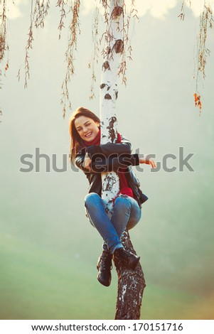 young happy woman hanging on tree misty winter day in park - stock photo