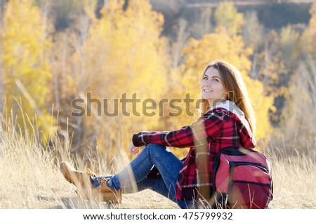 Young happy woman having fun outdoors sitting on the top of the hill. Backpacking tourism concept
