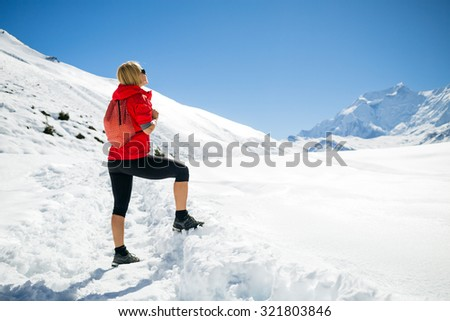 Young happy woman hiker looking at mountain peaks in winter mountains. Hiking and travel inspiration and motivation, beautiful landscape.Fitness healthy lifestyle outdoors on snow in Himalayas, Nepal. - stock photo