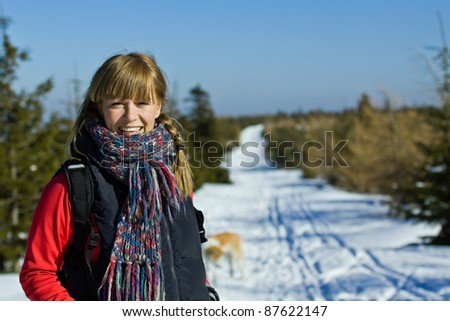 Young happy woman hiking in winter mountains, walking on snowy footpath - stock photo