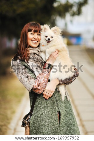 Young happy woman hold in hands small dog or puppy - outdoor portrait - stock photo