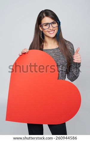 Young happy woman holdin Love symbol - big red heart shape, and showing approving sign - stock photo