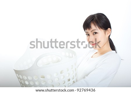 Young happy woman holding laundry basket. - stock photo