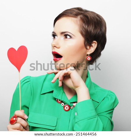 Young happy woman holding red  paper heart and ready for party  - stock photo