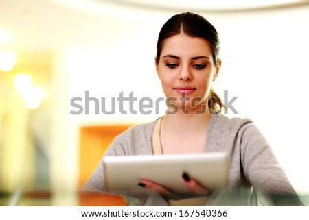 Young happy woman holding tablet computer at home - stock photo