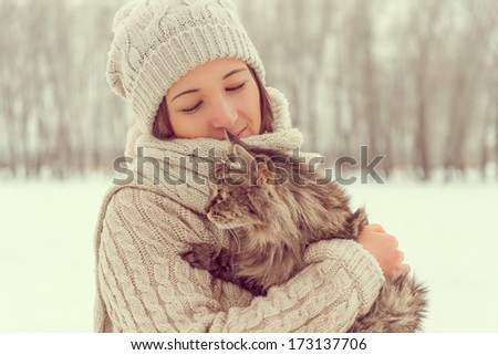 Young happy woman holds fluffy cat in winter - stock photo