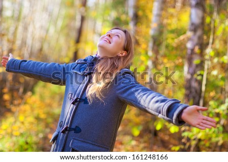 Young happy woman in autumn park. - stock photo
