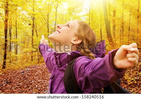 Young, happy woman in autumn with outstretched arms