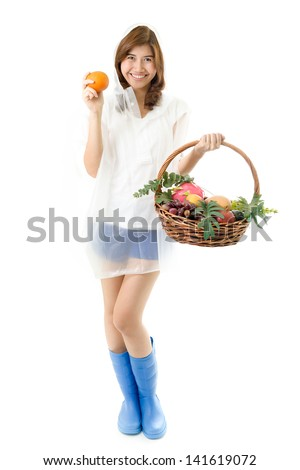 Young happy woman in blue boots and raincoat holding fruits basket. Healthcare concept.
