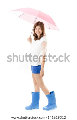 Young happy woman in blue boots with raincoat holding umbrella on white background. Raining season concept.