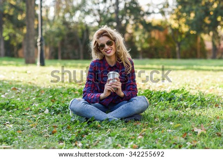 Young happy Woman in checkered shirt and blue jeans with toothy Smile and sunglasses. Blonde girl drinking coffee in park sitting on grass wearing casual clothes smiling - stock photo