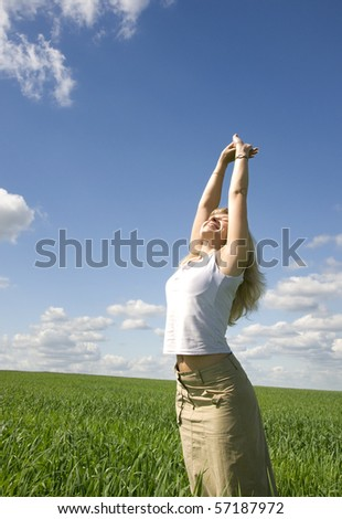 Young happy woman in field under blue sky - stock photo