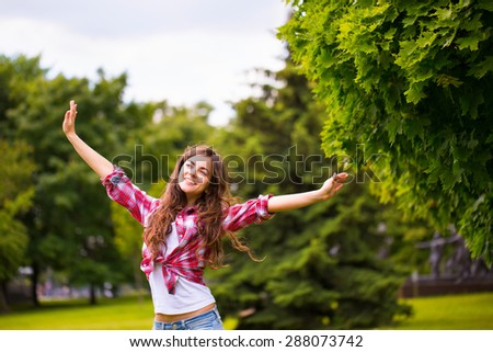 Young happy woman in the park - stock photo