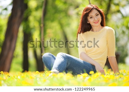 Young happy woman in the park with flowers