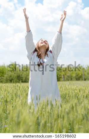 Young happy woman in traditional Ukrainian dress on summer outdoors background - stock photo