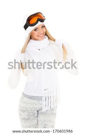 Young happy woman  in winter warm clothes and ski glasses stands on a white background. Winter sports. - stock photo