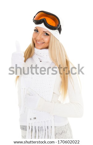 Young happy woman  in winter warm clothes and ski glasses stands on a white background. Winter sports.