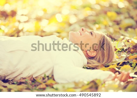 Young happy woman is relaxing in park in park, intentionally toned.