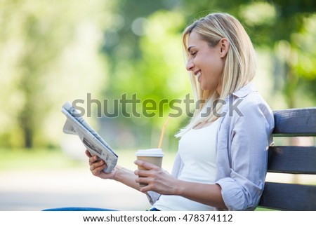 Young happy woman is sitting in park. She is reading newspapers and drinking coffee to go.