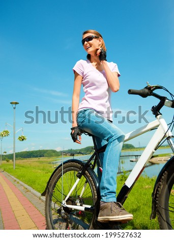Young happy woman is sitting on her bicycle, outdoor shoot - stock photo