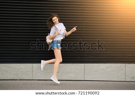 Young happy woman jump near city building wall