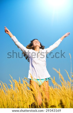 Young happy woman jumping in a summer field. - stock photo