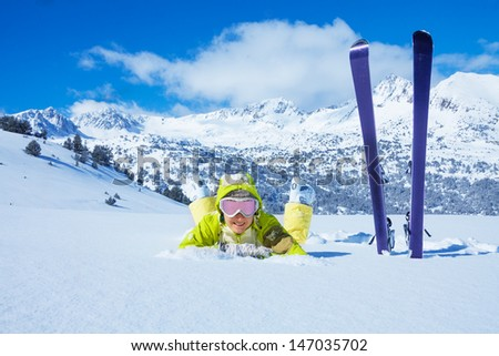 Young happy woman laying in snow with her ski standing by with mountain on background - stock photo