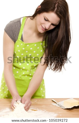 young happy woman mixing dough for baking on a table with white background - stock photo