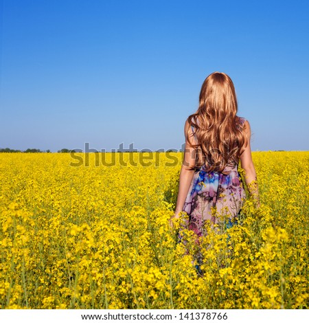 Young happy woman on blooming rapeseed field in summer - stock photo