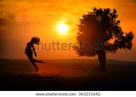 young happy woman on field in summer sunset