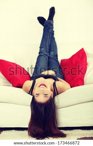 Young happy woman on sofa at home  - stock photo