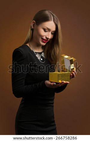 Young happy woman opening a gift box in studio - stock photo