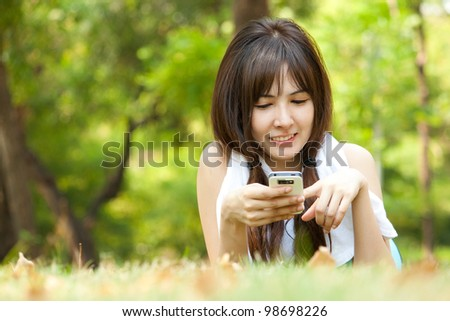 Young happy woman playing with her mobile while lying on the green grass at park - stock photo