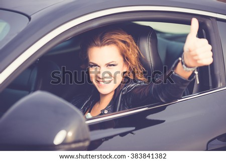Young happy woman showing Ok sign, thumb up in a sport car  - stock photo