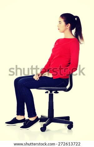 Young happy woman sitting on a chair - stock photo