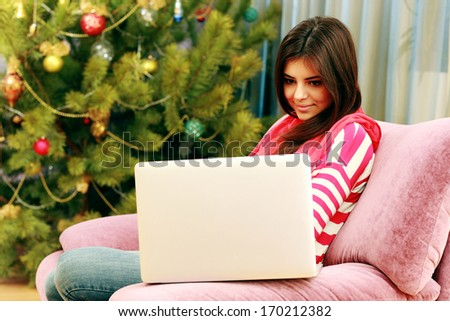 Young happy woman sitting on the sofa and looking on the laptop at home