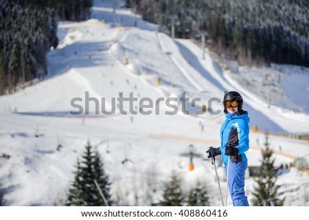 Young happy woman skier against ski slopes and ski-lift on background. Woman is wearing helmet skiing glasses gloves and blue ski suit. Winter sports concept. - stock photo