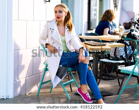Young happy woman smiling and relaxing at city cafe terrace, sunny weather, bright make up , stylish casual outfit, holidays, travel, vacation, joy. - stock photo
