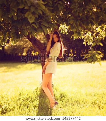 Young happy woman standing in yellow rapeseed field. - stock photo