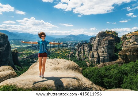 Young happy woman stands back to the rock with raised hands. Traveler enjoying the landscape with mountain, Monasteries of Meteora, Greece - stock photo