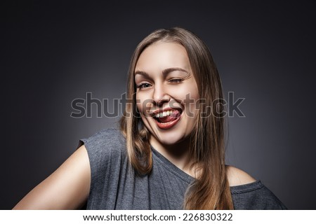 Young Happy Woman Sticking Out Her Tongue Over a Grey Background - stock photo