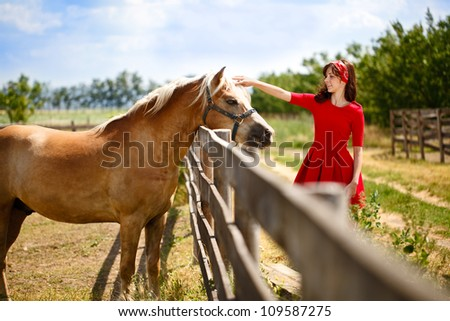 young happy woman stroked  her horse, friendship