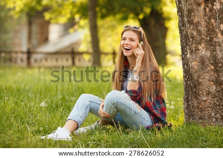 Young happy woman talking on cell phone sitting on grass in summer city park. Beautiful modern girl in sunglasses with a smartphone. Outdoor - stock photo