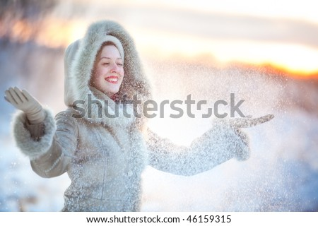 Young happy woman throwing up snow. - stock photo
